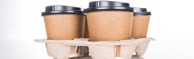 panoramic shot of paper cups with coffee in cardboard tray on white background