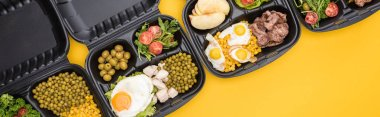 panoramic shot of eco packages with apples, vegetables, meat, fried eggs and salads isolated on yellow
