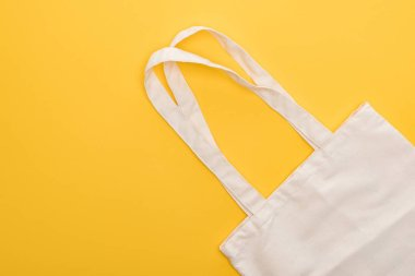 top view of cotton white eco friendly bag isolated on yellow