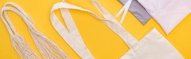 Top view of cotton eco friendly bags isolated on yellow, panoramic shot stock vector