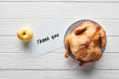 top view of roasted turkey, apple and card with thank you lettering served on white wooden table