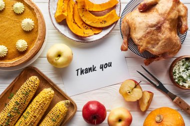 top view of roasted turkey, pumpkin pie and grilled vegetables served on white wooden table near thank you card