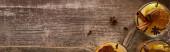Draufsicht auf warmen Birnenglühwein mit Gewürzen und getrockneten Zitrusfrüchten auf Holztisch, Panoramaaufnahme