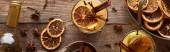 felső kilátás meleg körte forralt bor fűszerekkel és szárított citrusfélék fa asztalon, panorámás lövés
