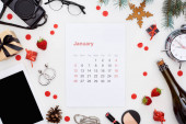 january calendar page, digital camera, alarm clock, digital tablet, champagne bottle, cosmetics, glasses, fir branch, fresh strawberry, christmas baubles isolated on white