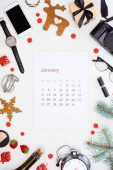 january calendar page, digital camera, alarm clock, smartphone, champagne bottle, cosmetics, glasses, fir branch, fresh strawberry,  christmas baubles isolated on white