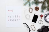 january calendar page, smartphone, digital camera, glasses, alarm clock, earphones, fir branch and cone, bracelets, earrings isolated on white