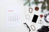 Január naptár oldal, okostelefon, digitális fényképezőgép, szemüveg, ébresztőóra, fülhallgató, fenyő ág és kúp, karkötők, fülbevaló elszigetelt fehér