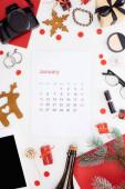 január naptár oldal, digitális fényképezőgép, pezsgős üveg, digitális tabletta, kozmetikumok, szemüveg, fenyő ág, fülbevaló, piros papír elszigetelt fehér