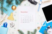 prosinec kalendář strana, digitální fotoaparát, vánoční ozdoby, jedle větev, náramkové hodinky, modrý papír, dřevěný blok s prosincovým nápisem, izolované na bílém