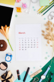 Fotografia march calendar page, digital tablet, lily flower, spikelets, cosmetics, donut, pencils, gift boxes, wristwatch, toy alarm clock, block with march inscription isolated on white