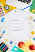 Fotografie september calendar page, laptop, apples, school supplies, multicolored paper, wooden block with september inscription isolated on white