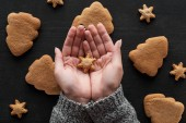 Fotografie partial view of woman holding snowflake cookie in hands