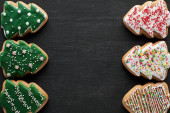 Fotografie flat lay with delicious glazed Christmas tree cookies on black background with copy space