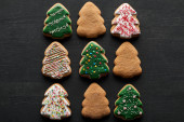 Fotografie flat lay with delicious glazed Christmas tree cookies on black background