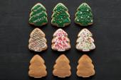 Fotografie byt ležel s lahodnou glazované vánoční strom cookies na černém pozadí
