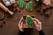 cropped view of woman putting Christmas tree cookie in gift box on wooden table