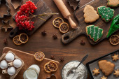 vrchní pohled na vánoční stromeček cookies v blízkosti ingrediencí a viburnum na dřevěném stole