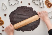 cropped view of woman holding rolling pin on raw dough for chocolate Christmas cookies on white background near anise, dough molds and dried citrus