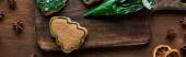 Fotografie top view of Christmas tree cookies, pastry bag and winter spices on wooden table, panoramic shot
