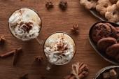 vrchní pohled na vánoční kakao se šlehačkou na dřevěném stole s anýzem, sušenkami a skořicí