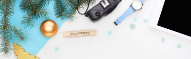 panoramic shot of digital tablet, fir branch, wristwatch, christmas baubles, wooden block with december inscripton isolated on white