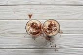 top view of cacao with whipped cream and cacao powder in mugs on white wooden table