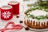 cukornád, karácsonyi pite cukormázzal és két csésze kávé fehér fa asztalon