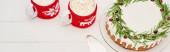 vrchní pohled na vánoční koláč s rozmarýnem a dva šálky kakaa s marshmallows na bílém dřevěném stole
