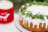 Fotografie Weihnachtskuchen mit Rosmarin und Preiselbeeren auf weißem Holztisch mit einer Tasse Kakao