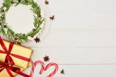 pohled shora na vánoční koláč, anýzová semínka, candy canes a dárkové krabice na bílém dřevěném stole