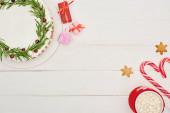 Weihnachtskuchen, Geschenke, Zuckerstangen und Tasse Kakao mit Marshmallows auf weißem Holztisch