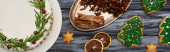 top view of christmas pie, spices and christmas tree cookies on dark wooden table