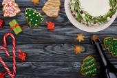 Fotografie vrchní pohled na vánoční koláč, láhev šampaňského, candy canes, dárky a sušenky na tmavém dřevěném stole