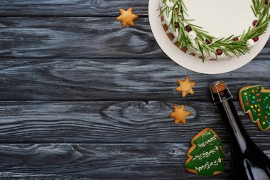 top view of christmas pie, bottle of champagne and christmas tree cookies on dark wooden table