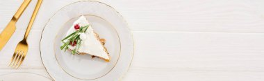top view of christmas pie piece with fork and knife on white wooden table