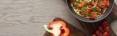 vrchní pohled na omeletu v pánvi na dřevěné desce s paprikou a rajčaty