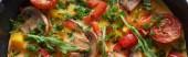 Fotografie vrchní pohled na domácí omeletu s houbami, rajčaty a zeleninou