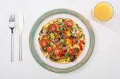 vrchní pohled na chutnou omeletu k snídani na bílém stole s džusem, vidličkou a nožem