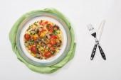 vrchní pohled na talíř s chutnou omeletou s rajčaty k snídani na bílém stole s ubrouskem, vidličkou a nožem