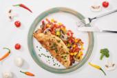 top view di piatto con gustosa frittata con verdure su tavola bianca con ingredienti, forchetta e coltello
