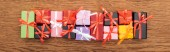 top view of small decorative gift boxes on wooden background, panoramic shot