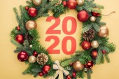 top view of paper 2020 numbers in christmas wreath with baubles on yellow background