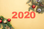 top view of paper 2020 numbers near christmas tree branches with baubles and cones on yellow background