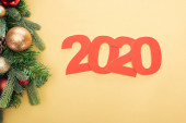 top view of paper 2020 numbers near christmas tree branch with baubles on yellow background