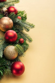 christmas tree branch with baubles on yellow background