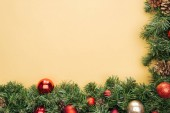 top view of christmas tree branch with red and golden baubles on yellow background