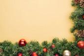 horní pohled na vánoční strom větev s červenými a zlatými ozdoby na žlutém pozadí