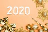 horní pohled na bílá 2020 čísla v blízkosti zlaté vánoční dekorace na oranžovém pozadí