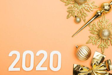 Top view of white 2020 numbers near golden christmas decoration on orange background stock vector